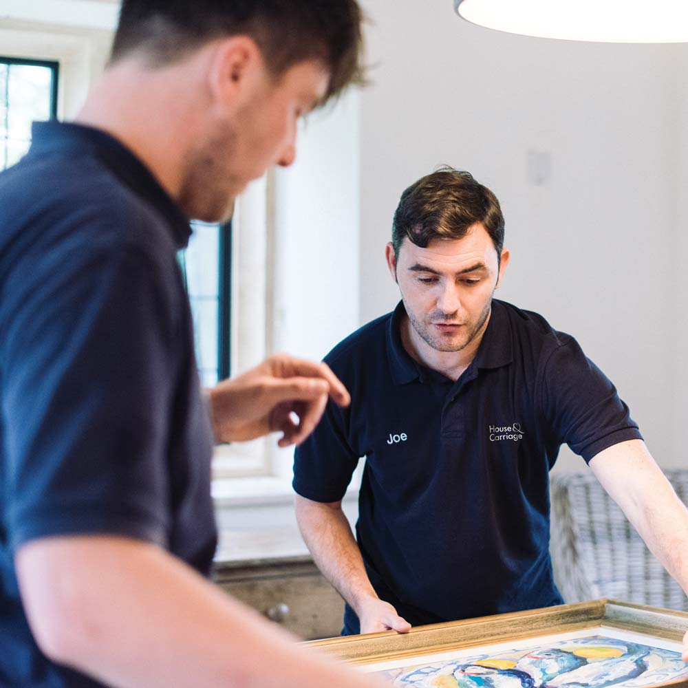 Two removal men packaging a piece of fine art on a table